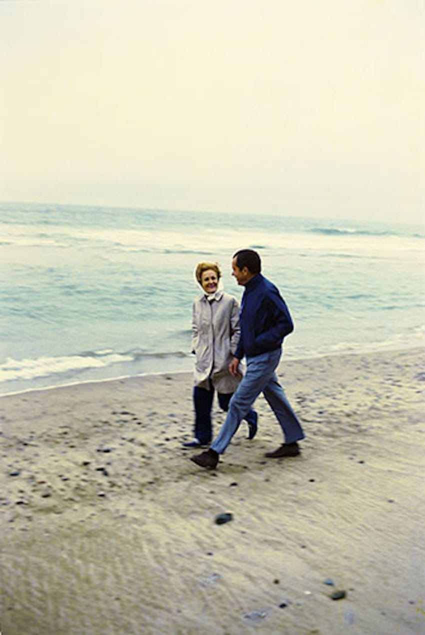 "President and Mrs. Nixon enjoy a walk on the beach near the San Clemente ""Western White House"""